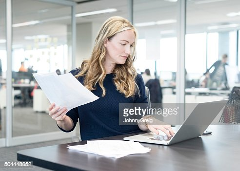 Businesswoman holding document and using laptop in modern office