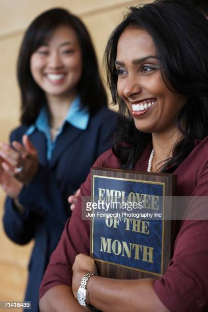 Businesswoman holding Employee of the Month plaque