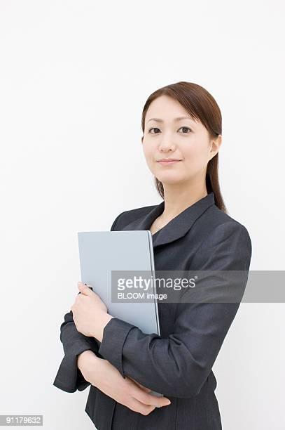 Businesswoman holding file folder, studio shot, portrait