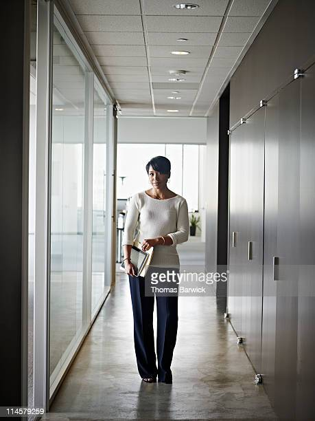 Businesswoman holding folder and digital tablet