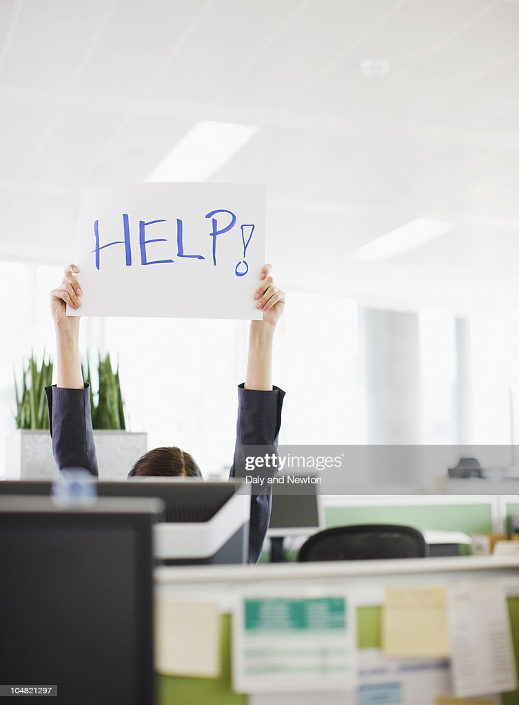 Businesswoman holding Help sign overhead in office : Stock Photo