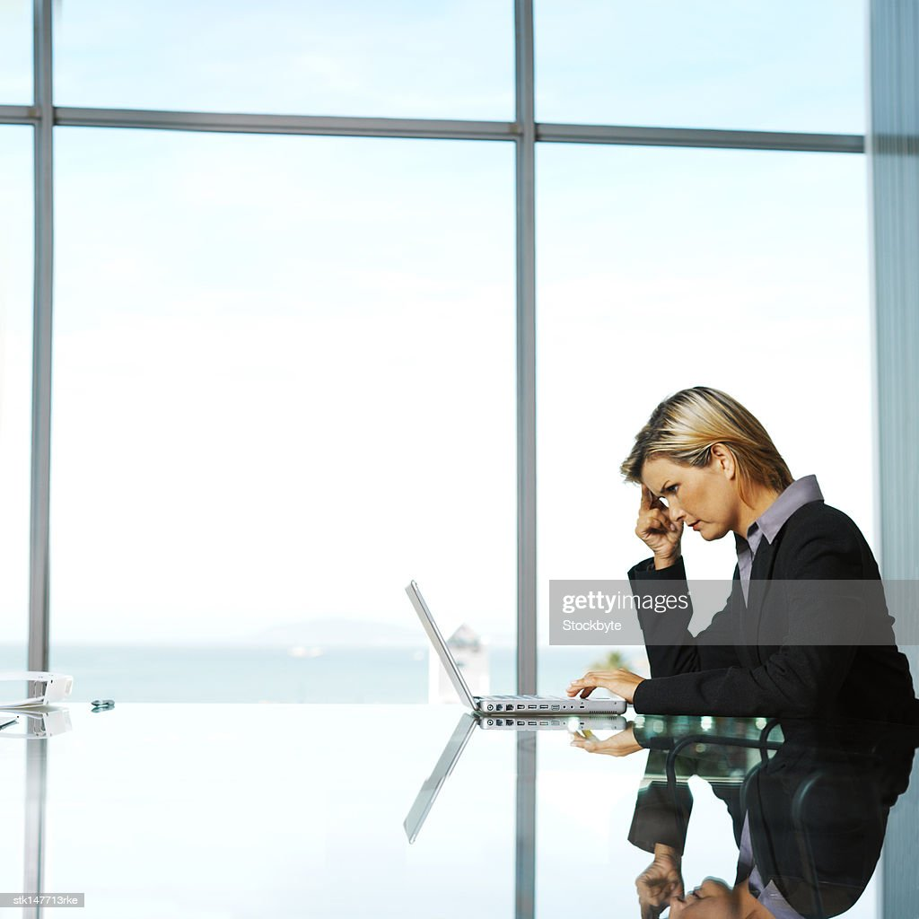 businesswoman holding her head and sitting in front of a laptop : Stock Photo
