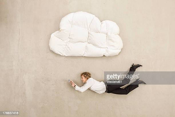Businesswoman holding mobile phone and flying below cloud shape pillow