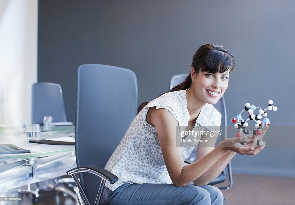 Businesswoman holding molecule model in conference room : Stock Photo