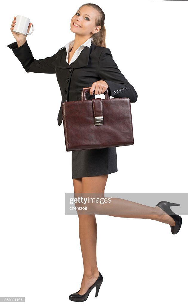 Businesswoman holding mug and briefcase : Stock Photo