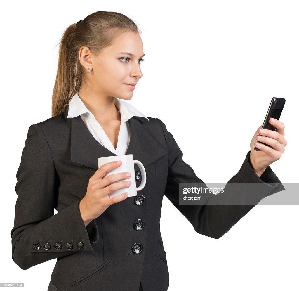 Businesswoman holding mug and using mobile phone : Stock Photo