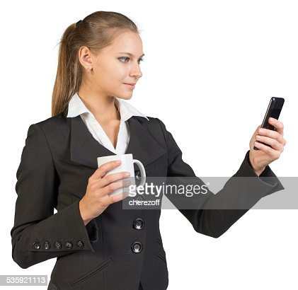 Businesswoman holding mug and using mobile phone : Stock Photo