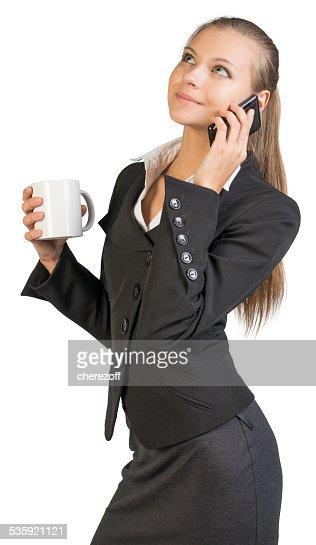 Businesswoman holding mug, talking on the phone : Stock Photo