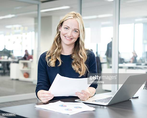Businesswoman holding paperwork at desk, smiling toward camera
