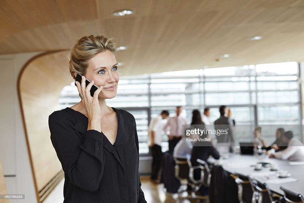 Businesswoman holding phone in conference room : Stock Photo