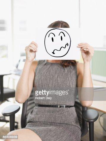 Businesswoman holding picture of frustrated face : Bildbanksbilder