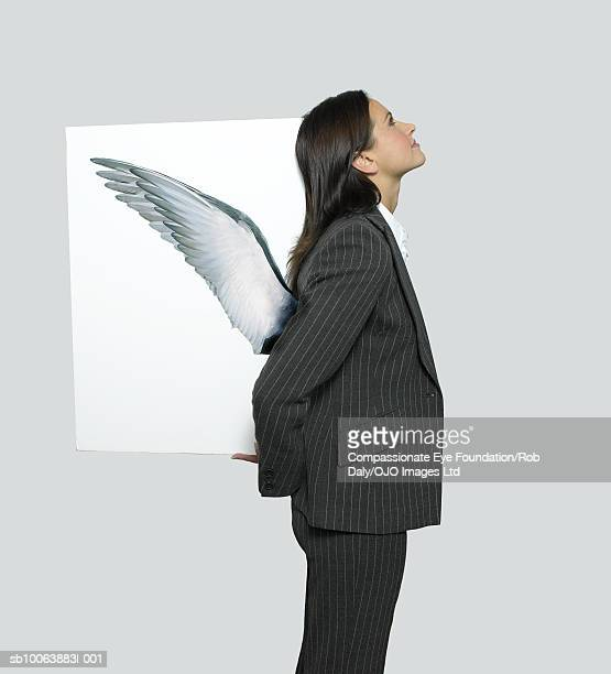 Businesswoman holding picture of wings on back, side view