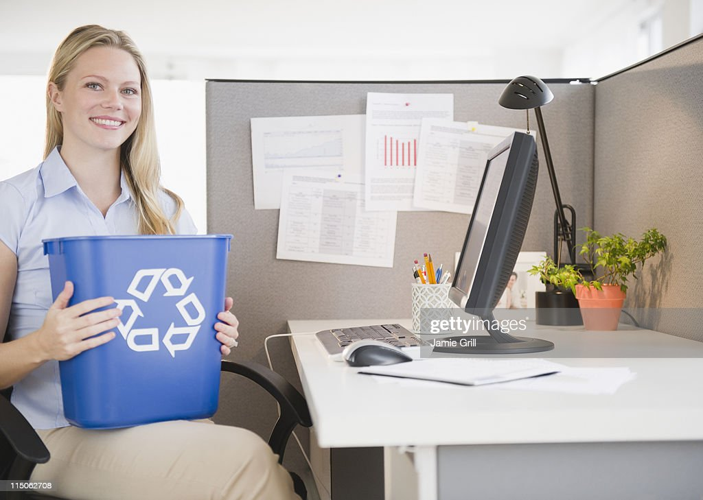 Businesswoman holding recycling bin at desk : Stock Photo