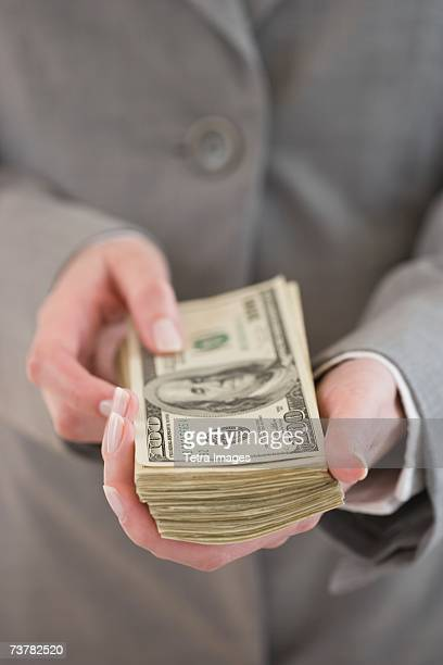 Businesswoman holding stack of money