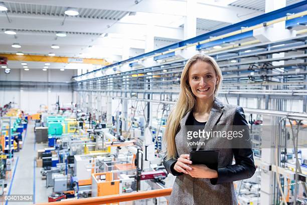 Businesswoman holding tablet on top of production line