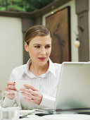 Businesswoman holding teacup in restaurant, looking at laptop