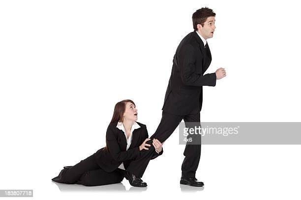 Businesswoman holding the leg of a businessman