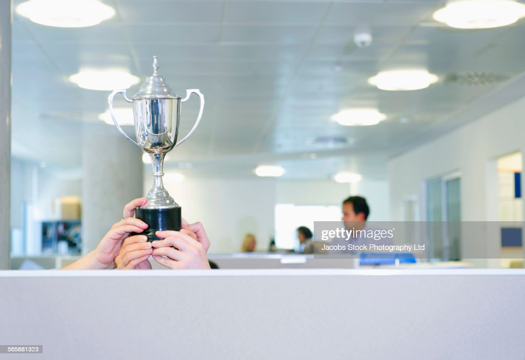Businesswoman holding trophy over office cubicle : Stock Photo