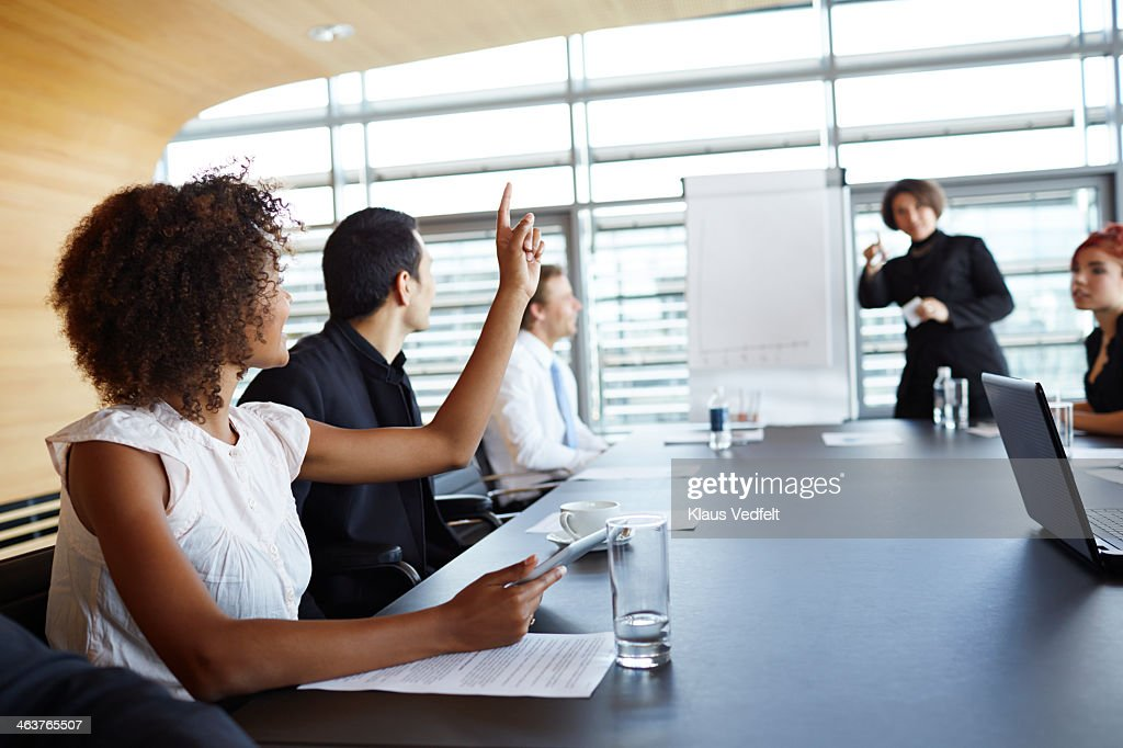 Businesswoman holding up hand at meeting : Stock Photo
