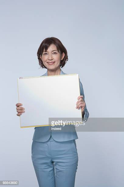 Businesswoman holding up whiteboard, portrait