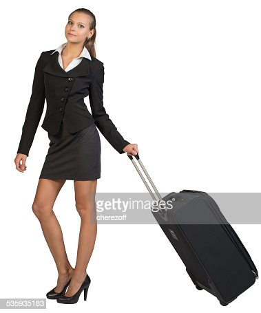 Businesswoman holding wheeled bag in moving position : Stock Photo