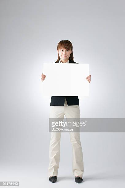 Businesswoman holding white board, studio shot