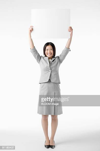 Businesswoman holding whiteboard over head, studio shot