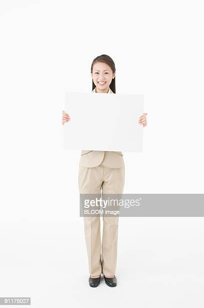 Businesswoman holding whiteboard, smiling