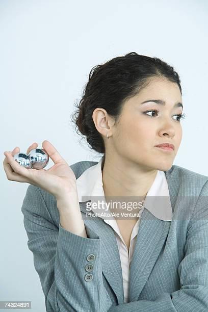 Businesswoman holding yin yang balls