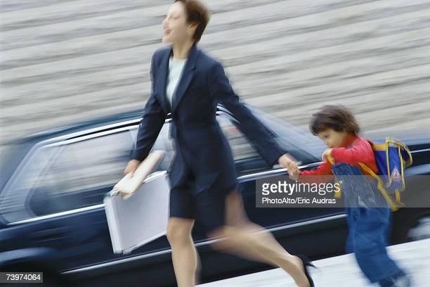 Businesswoman hurrying, holding little boy's hand