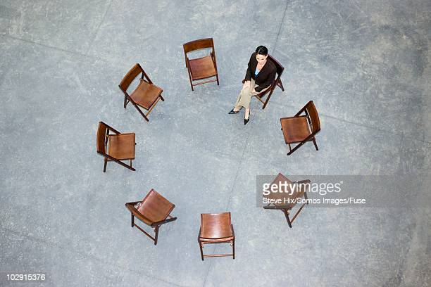 Businesswoman in a circle of empty chairs