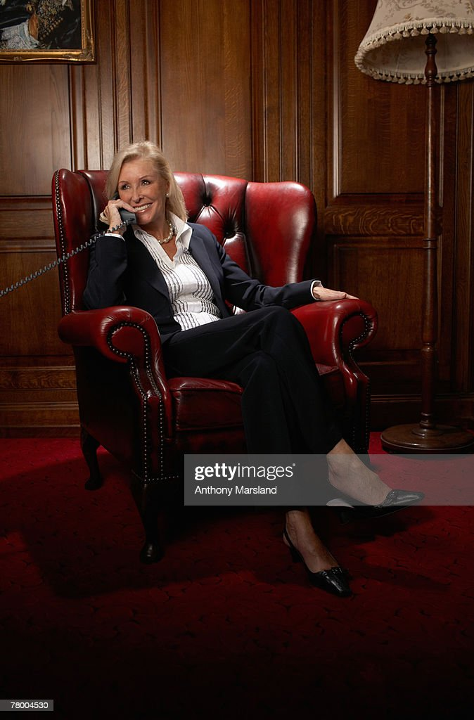 Businesswoman in a comfy leather chair with a phone : Stock Photo