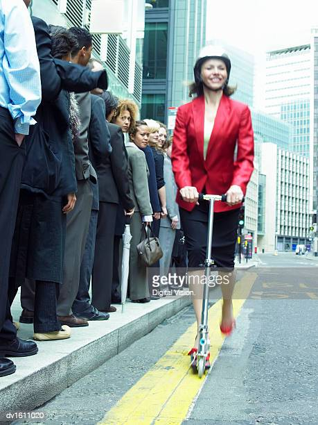 Businesswoman in a Red Jacket Riding past People in a Line on a Push Scooter