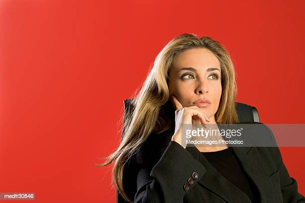 Businesswoman in black suit looking away and sitting in office chair with hand on face, close-up