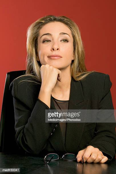 Businesswoman in black suit with hand on chin and glasses on desk, close-up
