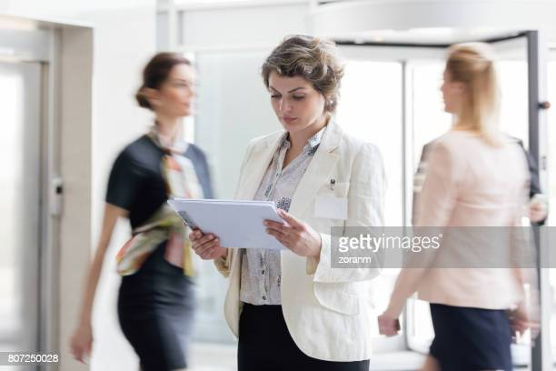Businesswoman in busy lobby