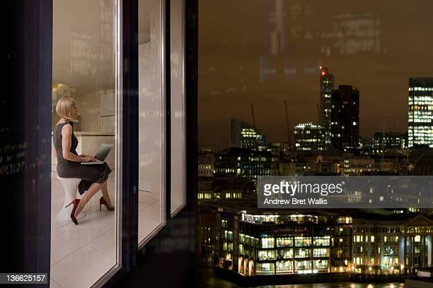 Businesswoman in city aprtment at dusk uses laptop
