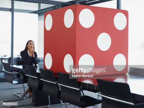 Businesswoman in conference room looking at giant dice : Stock Photo