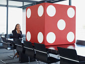 Businesswoman in conference room looking at giant dice