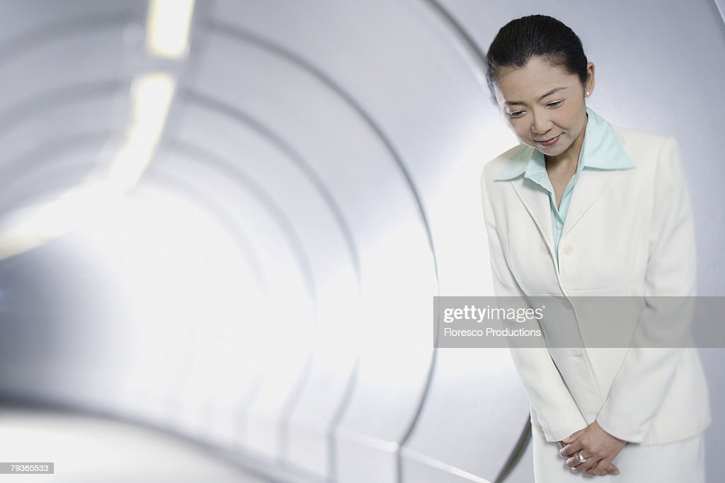 Businesswoman in corridor bowing at camera