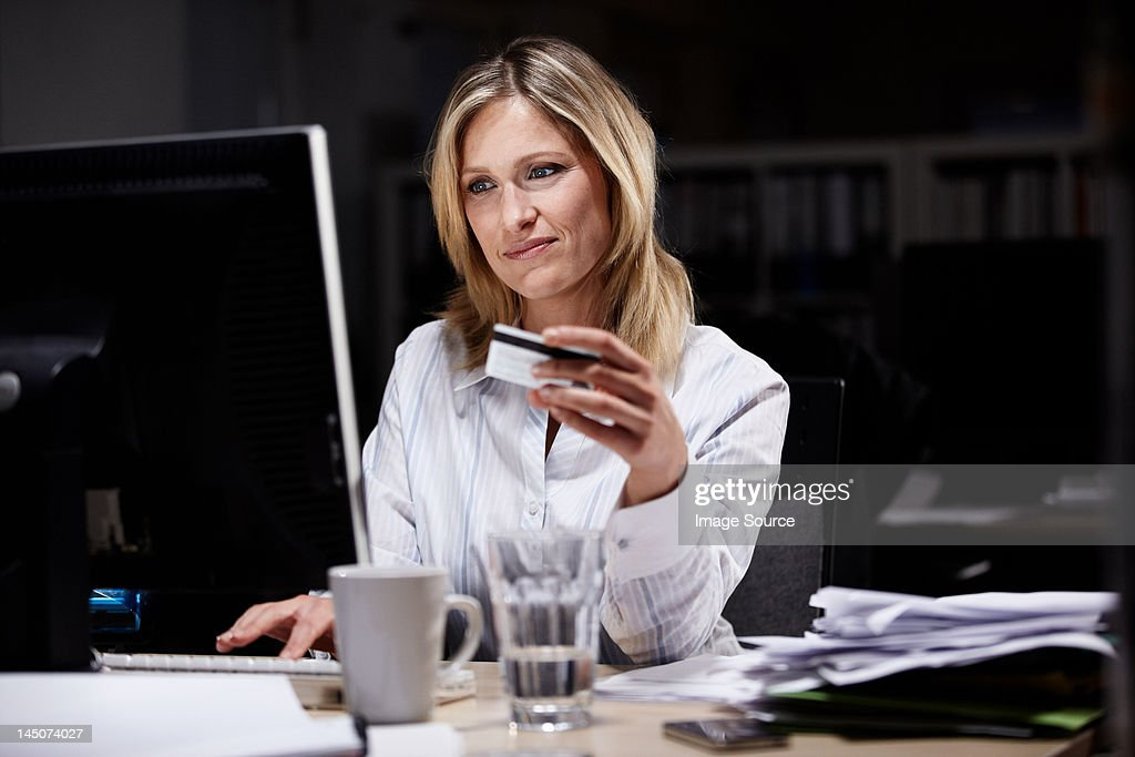 Businesswoman in dark office, using credit card online : Stock Photo