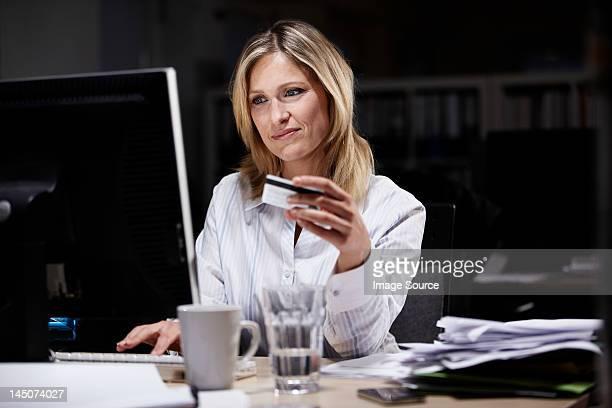 Businesswoman in dark office, using credit card online