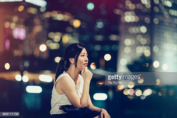 Businesswoman in deep thought in city at night