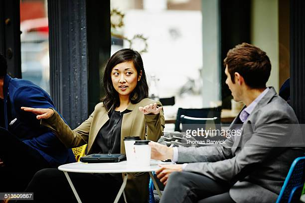 Businesswoman in discussion with colleague at cafe