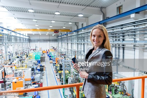 Businesswoman in factory working on digital tablet