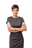 """""""Short haired businesswoman wearing a gray, belted dress. She is standing with arms crossed and is isolated on a white background. Vertical shot."""""""