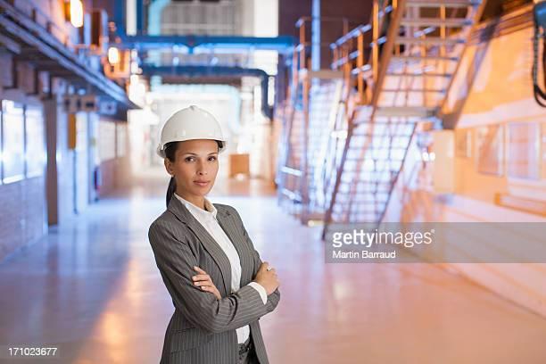 Femme d'affaires dans le chapeau dur debout en usine