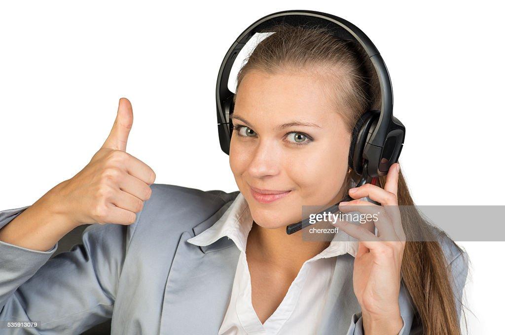 Mujer de negocios mostrando pulgar arriba en auriculares : Foto de stock