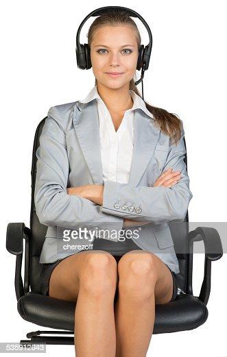 Empresaria en auriculares sentado en silla de oficina, sus brazos cruzados : Foto de stock