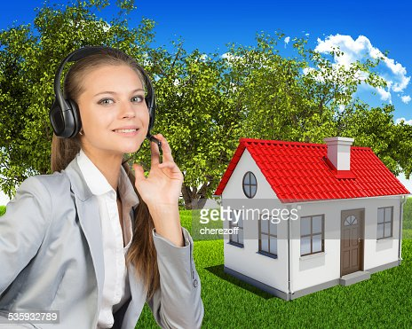 Businesswoman in headset, small house and green landscape as backdrop : Stock Photo